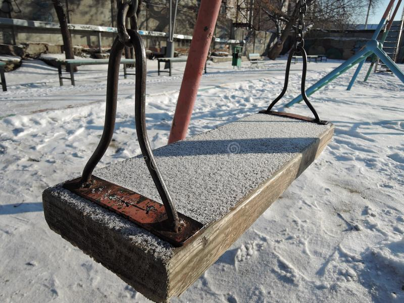 Empty swing in winter time with snow stock image
