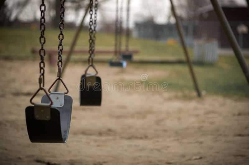 Empty Swings at Playground on Dull Day stock photo