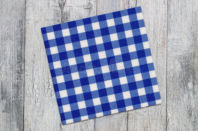 Empty table background. Top view of a empty blue and white checkered kitchen cloth, textile, tablecloth or napkin on a rustic royalty free stock photography