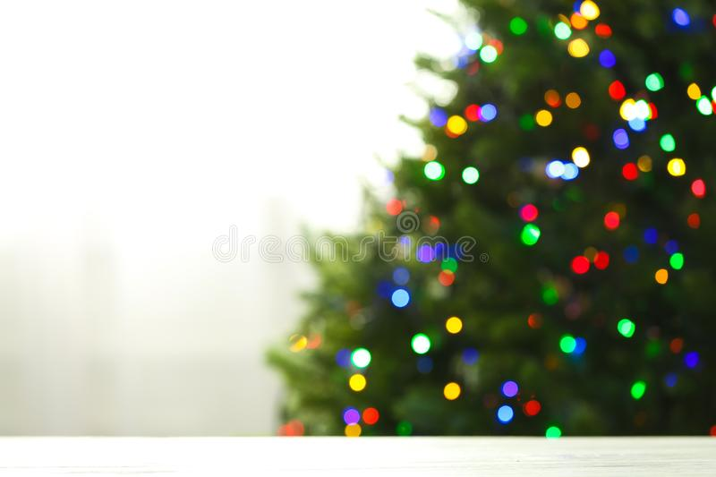 Empty table and blurred fir tree with colorful Christmas lights on background, bokeh effect. Space for design royalty free stock photography