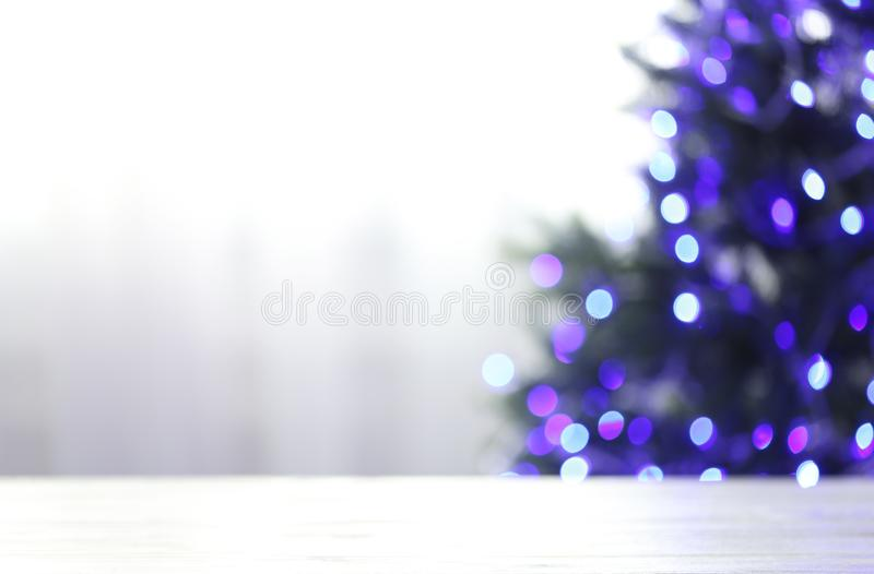 Empty table and blurred fir tree with violet Christmas lights on background. Space for design. Empty table and blurred fir tree with violet Christmas lights on stock images