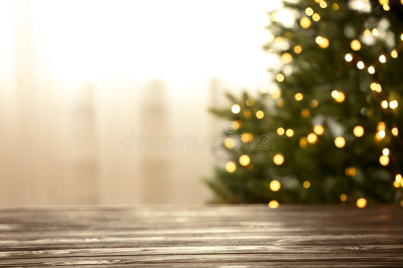 Empty table and blurred fir tree with yellow Christmas lights on background, bokeh effect. Space for design royalty free stock photo