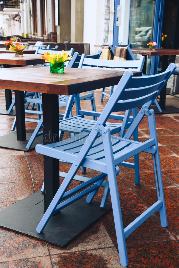 Empty table in a cafe on the street. Beautiful blue rustic chair stock photography