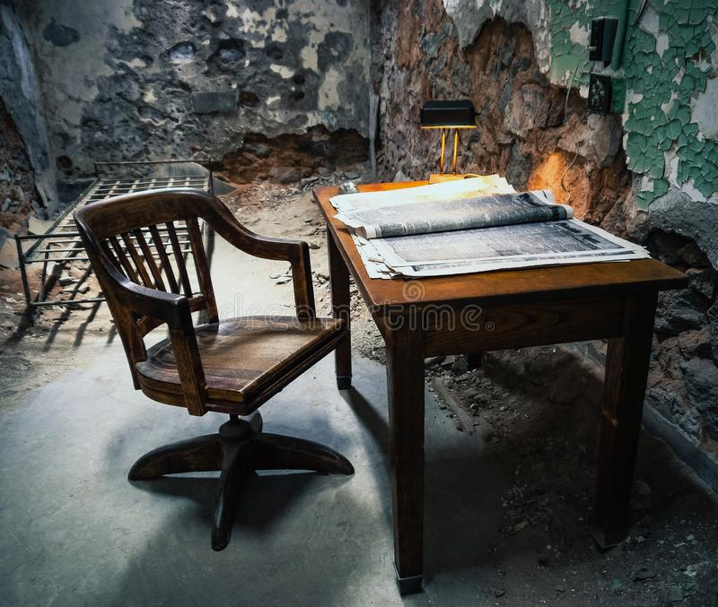 Empty table and chair in the old prison stock image