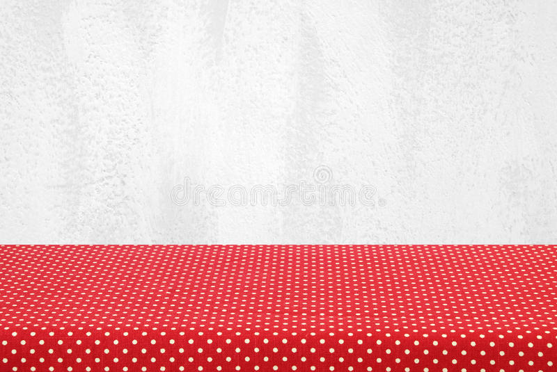 Empty table covered with red polka dot tablecloth over white cement wall background royalty free stock images