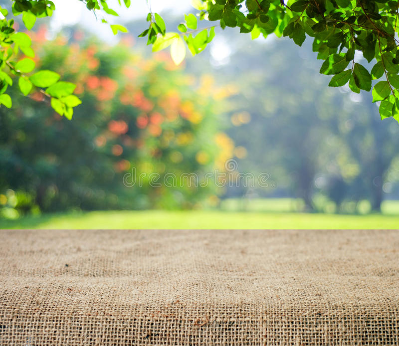 Empty table covered with sackcloth over blurred trees with bokeh background royalty free stock photography