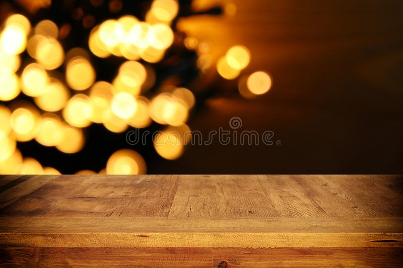 Empty table in front of black and gold glitter lights background. For product display montage.  stock image