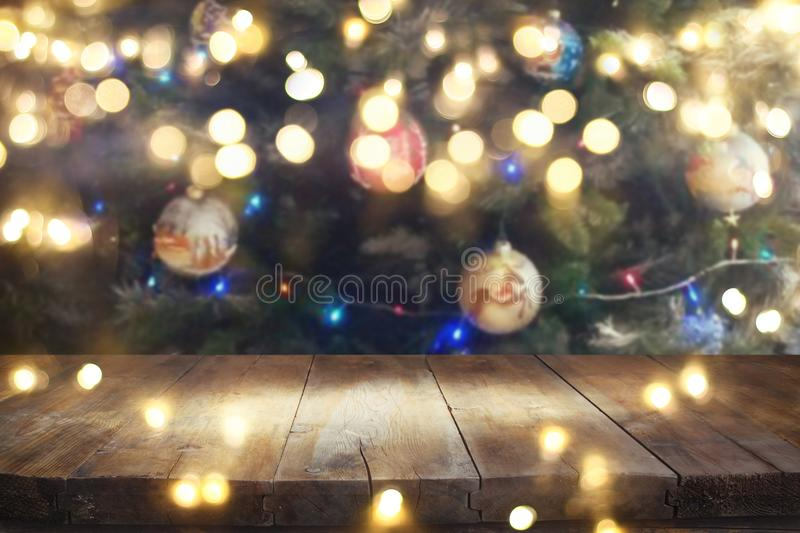 Empty table in front of christmas tree with decorations background. For product display montage stock photo