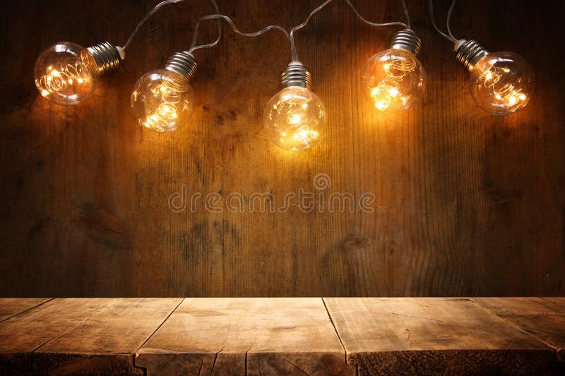 empty table in front of Christmas warm gold garland lights on wooden background. stock photography