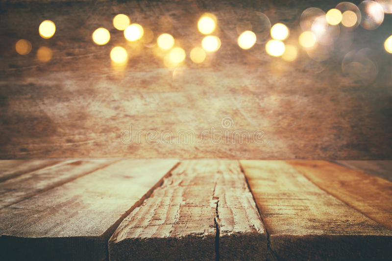 empty table in front of Christmas warm gold garland lights royalty free stock images