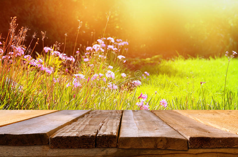 Empty table in front of spring beautiful field flowers. Empty rustic table in front of spring beautiful field flowers. product display and picnic concept royalty free stock photos