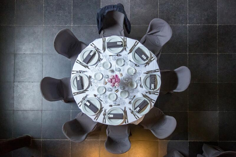 Empty table at a party. In a wedding reception. The table is whit with flowers and candles on it and the chairs are dark grey. It forms an abstract form royalty free stock images