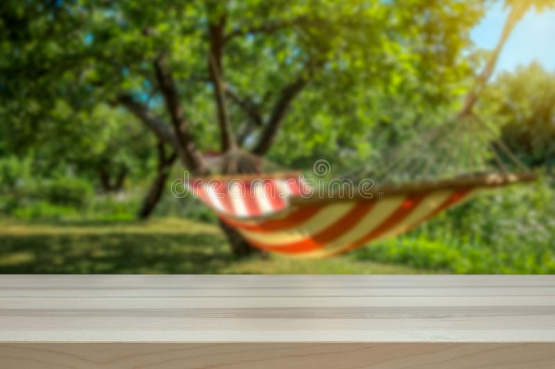 Concept for holiday and lazy days. Hammock in a sunny green garden blurred in the royalty free stock photo