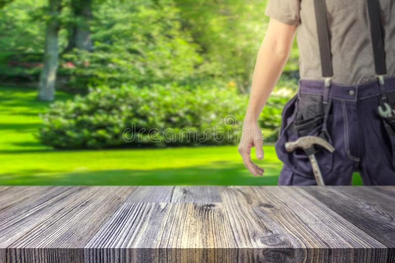 Handyman / craftsman in green garden blurred in the background royalty free stock images