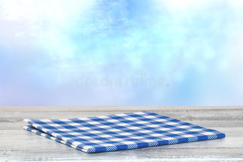 Empty table top summer background. Closeup of a empty blue checkered tablecloth or napkin on a rustic bright gray table over vector illustration