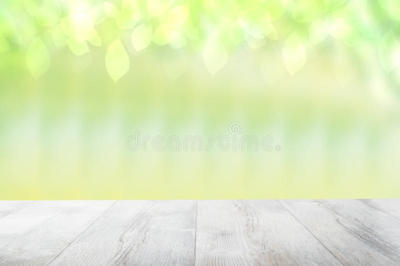 Empty table top summer background. Empty rustic wooden bright table top in front of a beautiful abstract light green spring stock photos