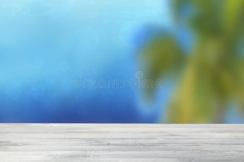 Empty table top tropical summer background. Empty rustic wooden bright table top in front of beautiful abstract blue ocean, sky stock photography
