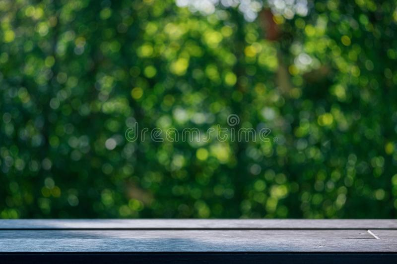 Empty table top wood table with fresh green abstract blurred trees of nature park background and summer season for product stock photography