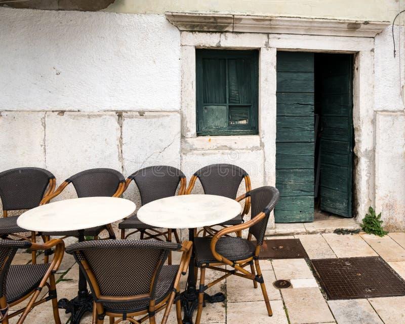 Empty tables of a cafeteria, open door in Cres. Empty tables of a cafeteria, open old green wooden door in Cres Croatia in spring royalty free stock photography