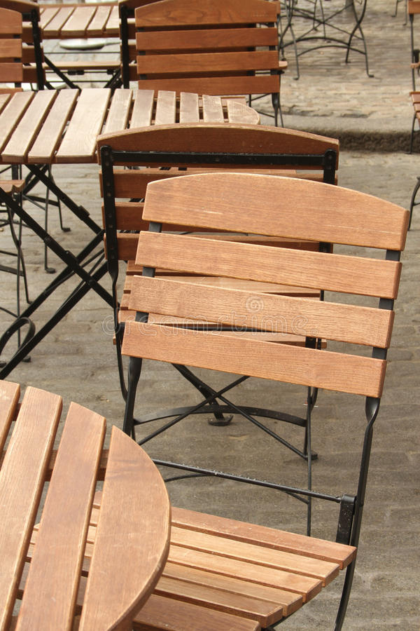 Empty tables at a sidewalk cafe. Empty wooden tables and chairs at a sidewalk cafe royalty free stock photo