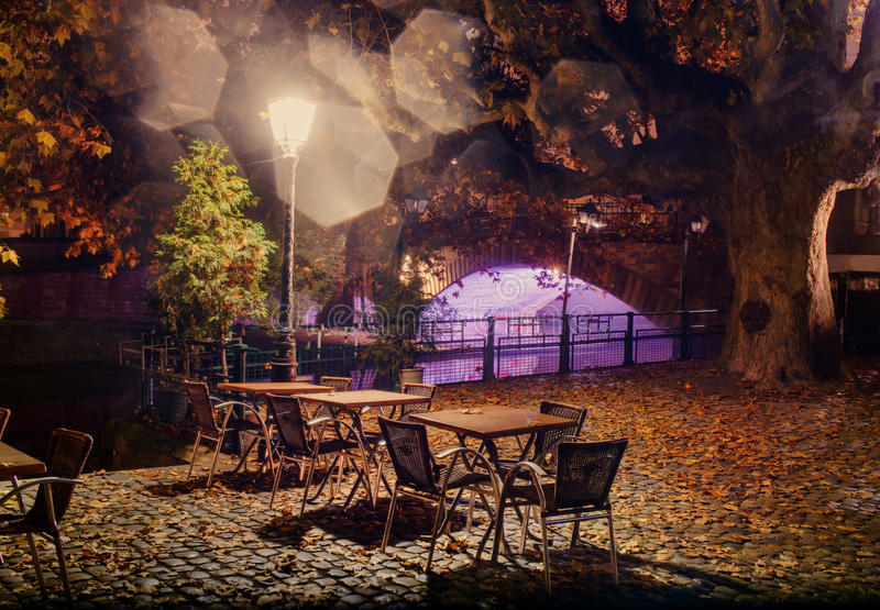 Empty tables under a lamp at night in the fog on the city waterfront. Empty tables under lamp at night in fog city promenade in autumn fallen leaves cobblestone royalty free stock photos