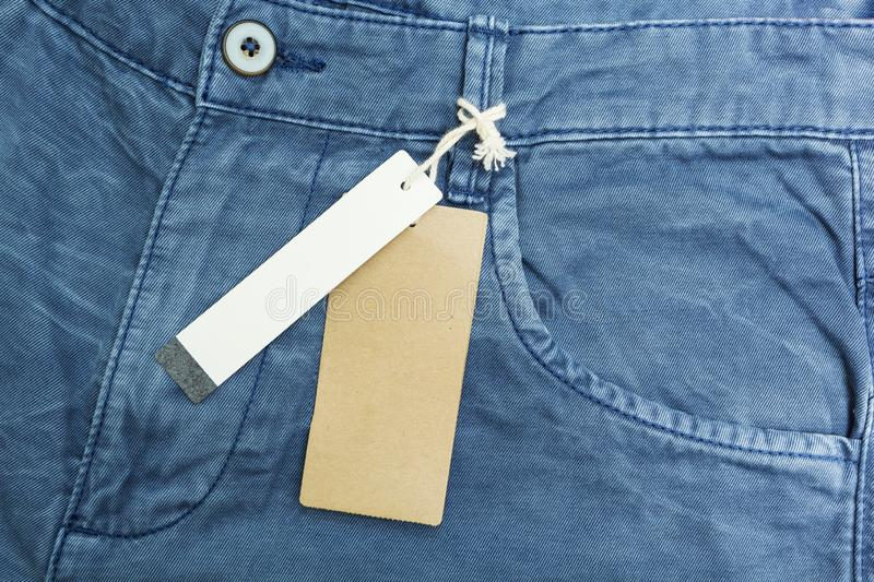 Empty tag on the background of blue denim pants.  stock image