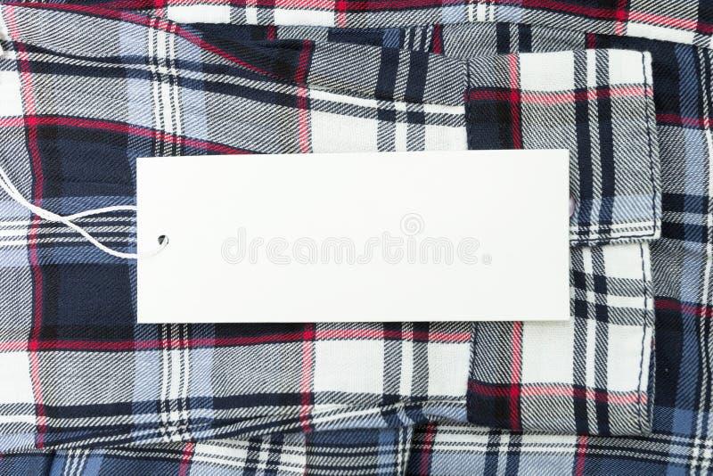 Empty tag blanco en tela con un modelo cuadrado Espacio vac?o para el texto fotos de archivo