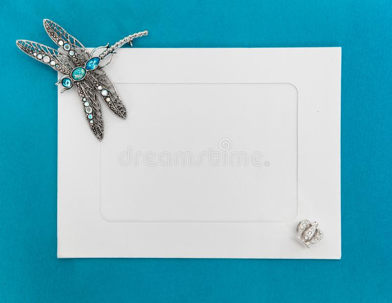 An empty template with white paper frame on blue background, decorated with jewelry. Silver dragonfly brooch at the corner of the stock photo