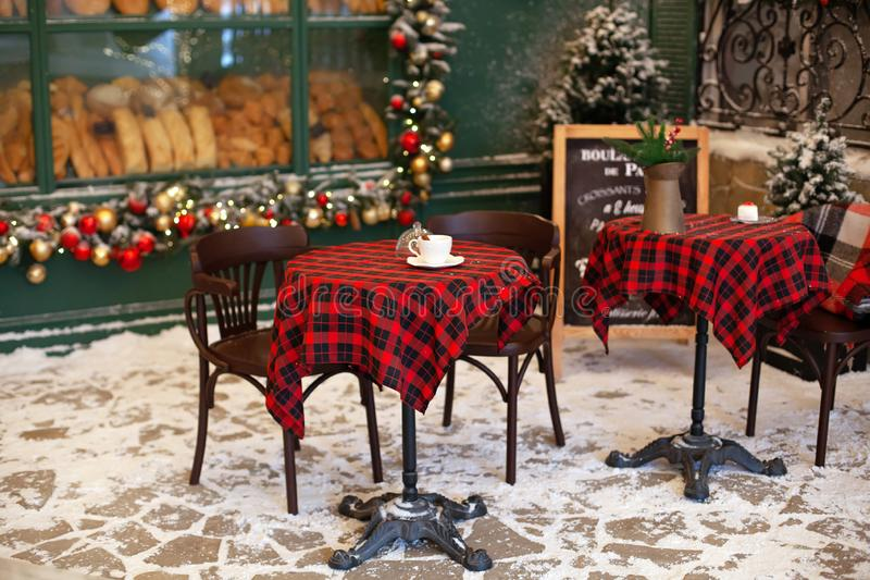 Empty terrace of cafe and restaurant with tables and chairs decorated for Christmas. Stylish Christmas decorations garlands and fi. R branches on windows of cafe royalty free stock photo