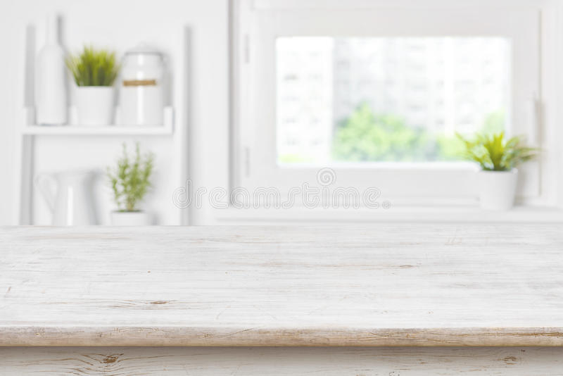 Empty textured wooden table and kitchen window shelves blurred background royalty free stock images