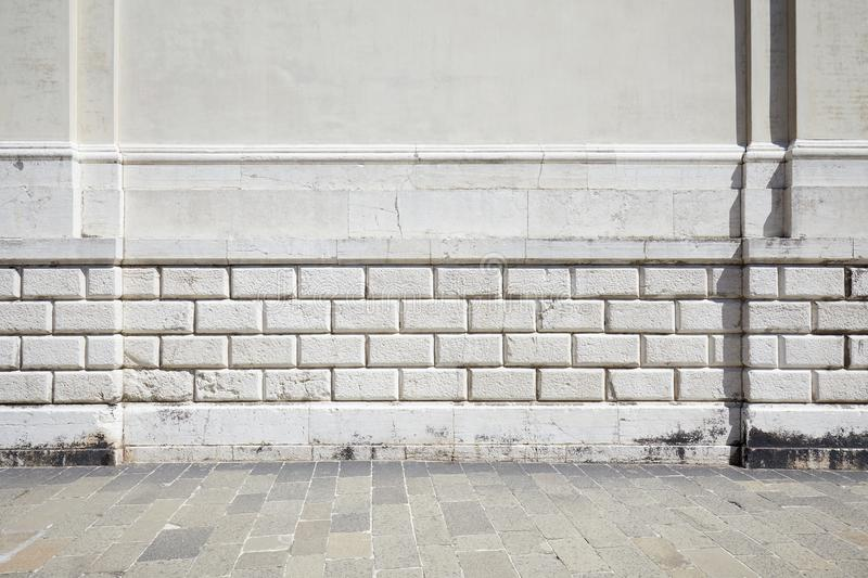 Empty tiled stone sidewalk and white ancient wall royalty free stock image