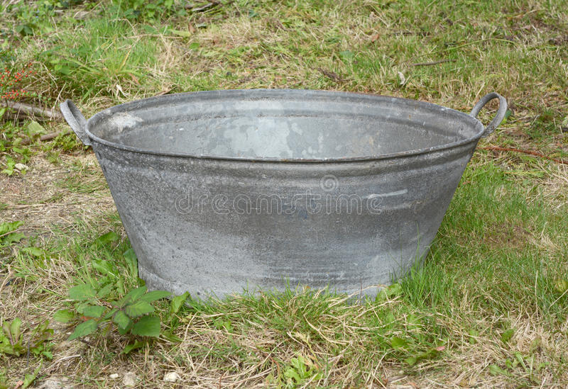 Empty tin bath. Standing on rough grass and weeds royalty free stock photos