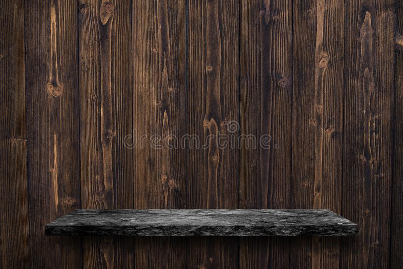 Empty top of black marble stone table on wooden plank wall background. For product display royalty free stock photography