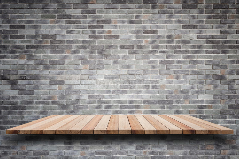 Empty top wooden shelves and stone wall background royalty free stock photo