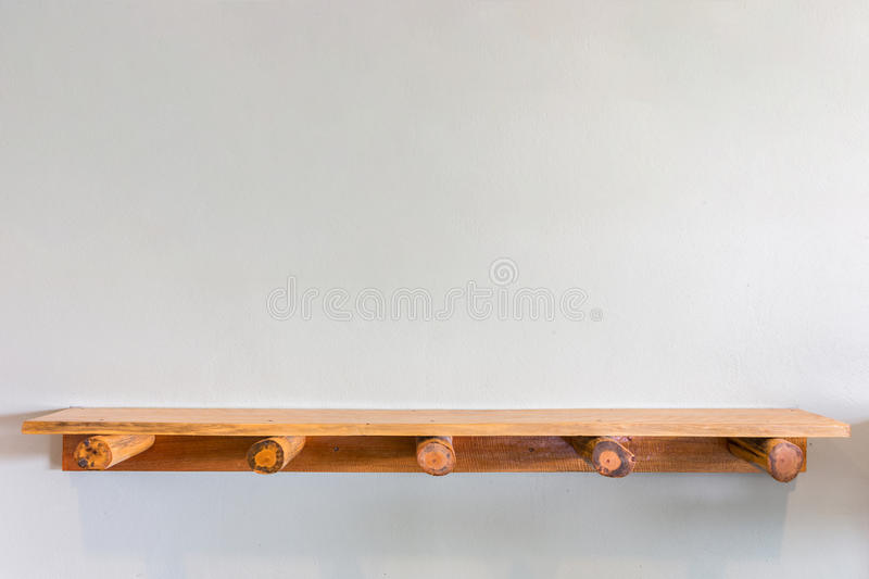 Empty top wooden shelves on white cement wall stock photos
