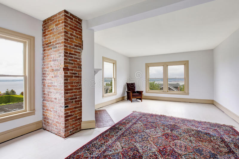 Empty traditional room interior in white tones with brick fireplace and rug stock image
