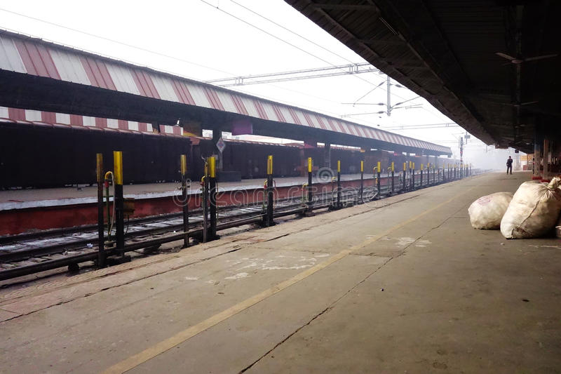 Empty Train Station. A single person stands at the end of an empty platform in an indian railway station in north india. This image gives a deep feeling of what royalty free stock images