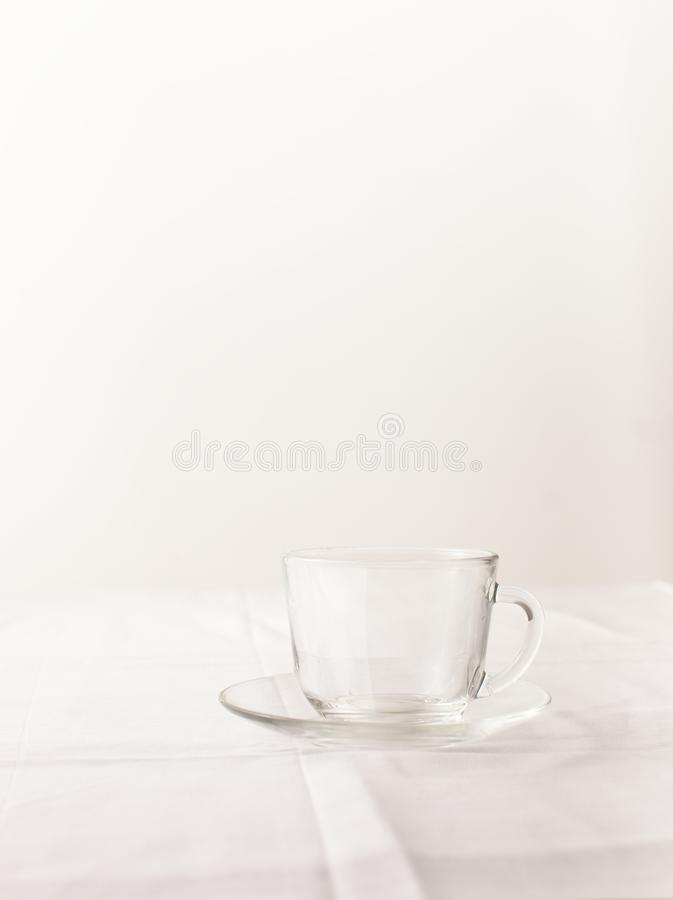 Empty transparent glass Cup with tea on white. An empty Cup of tea on the table with a white tablecloth. Place for text. Background image stock photos