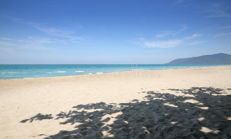 Empty tropical sandy beach, blue sky, shadow of the tree, Na Dan Beach in Nakhon Si Thammarat province of Thailand. Empty tropical sandy beach, blue sky, shadow royalty free stock image