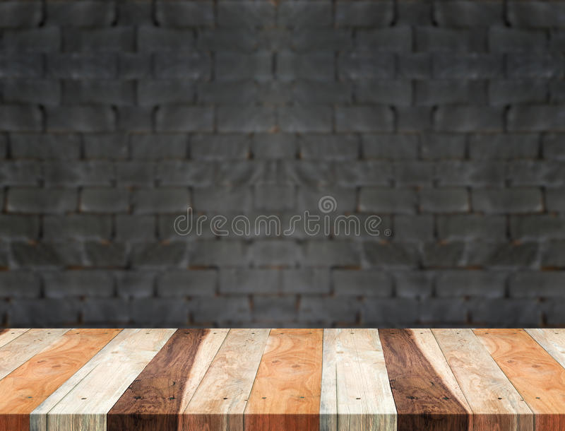Empty tropical wood table and blurred black brick wall background. product display template.Business presentation.  royalty free stock photo