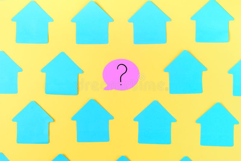 Empty turquoise stickers in the shape of a house, on a bright yellow background. In the center is a pink sticker in the stock photo