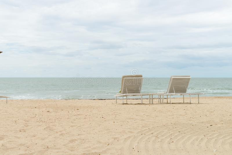 Empty two beach chairs on a beautiful beach at sunny day - vacation in summer time.  stock photos