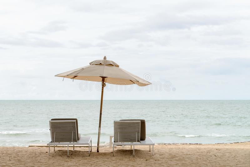 Empty two beach chairs and umbrella on a beautiful beach at sunny day - vacation in summer time royalty free stock photos