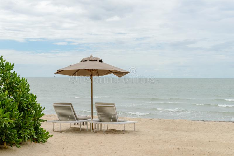 Empty two beach chairs and umbrella on a beautiful beach at sunny day - vacation in summer time.  stock photography