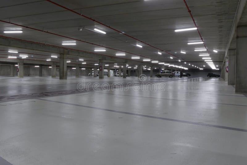 Empty underground car park illuminated at night stock image