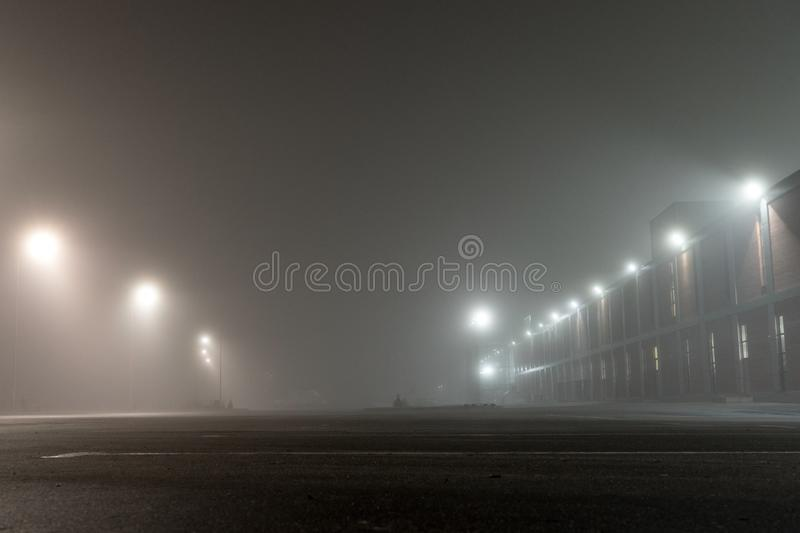 Empty urban car parking and streetlights at foggy night. Old Industrial brick building and lanterns on lonely street.  royalty free stock photography