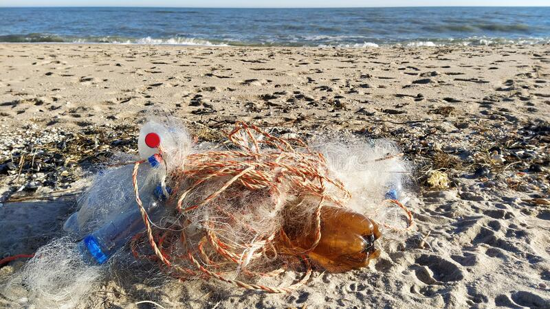 Empty used dirty plastic bottles, bags, fishing net,garbage dumped on the sea beach sand.Environmental pollution problem royalty free stock photo