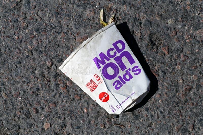 Empty Used McDonal`s Soda Cup Laying on Asphalt Road in Helsinki. Used, empty McDonald`s soda/lemonade cup laying on the ground in Helsinki, Finland, July 2019 stock photography