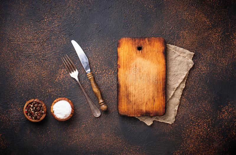 Empty vintage cutting board with spices and cutlery royalty free stock images