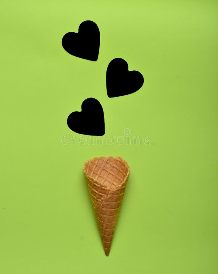 Empty waffle horn and black hearts on a green paper background, minimalist trend, top view. Empty waffle horn and black hearts on a green paper background stock photos